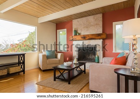 Classic red and white living room interior with view window and hardwood floor. Fitted fire place and red, blue pillows on sofa, couch with hand-woven natural colored fine sisal runner, rug.  - stock photo