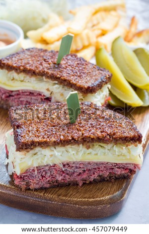 Classic reuben sandwich with corned beef, swiss cheese, sauerkraut and thousand island dressing on pumpernickel bread, served with dill pickle spear and potato chips, vertical - stock photo