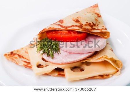 Classic russian pancake with ham, cheese and tomato - stock photo