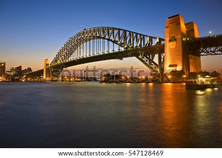 Classic shot of Sydney Harbour Bridge, illuminated at twilight.