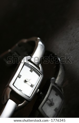 Classic silver watch on a piece of black granite.  Reflection on granite.  Shallow D.O.F - stock photo
