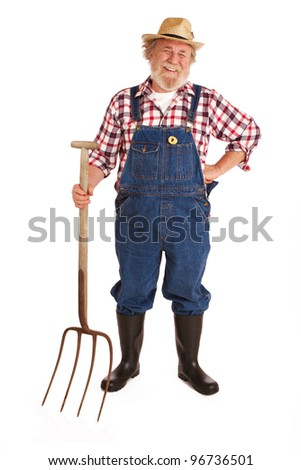 Classic smiling senior farmer with straw hat, plaid shirt, bib overalls, holding hay fork. Vertical layout, isolated on white background with copy space. - stock photo