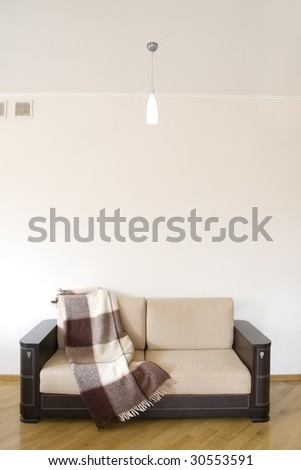 classic sofa covered by rug on the wooden floor - stock photo