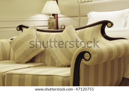 classic sofa in a stylish hotel room with bed and lamp in the background; high dynamic range image - stock photo