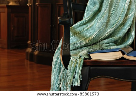 Classic still life of dark wood armchair with old book and handmade afghan in elegantly furnished living room. Conceptual image for solitude and relaxation.  Closeup with shallow dof. - stock photo