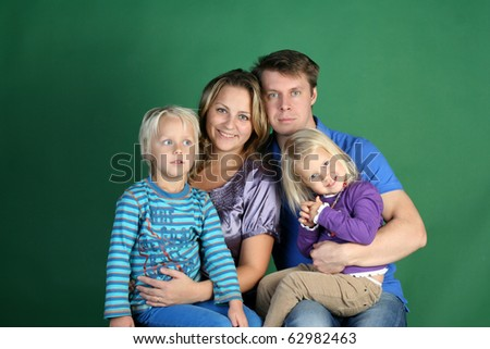 Classic Studio Family Portrait of four. Smiling mommy, daddy, funny cute daughter and 5 years dreaming boy - stock photo