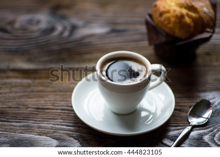 Classic style espresso shot with chip muffin on old wooden table. - stock photo