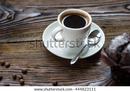 Classic style espresso shot with chocolate chip muffin and coffee beans on old wooden table. - stock photo
