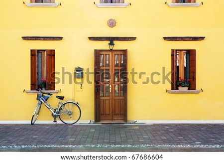Classic style house entrance (yellow walls, wooden door and windows decorates with flowerpots) and lonely bicycle - stock photo
