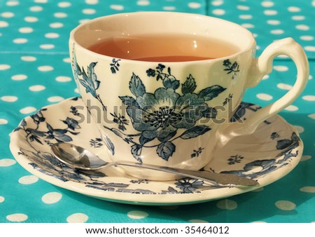 Classic tea cup with blue flowers and a background with polkadot tablecloth - stock photo