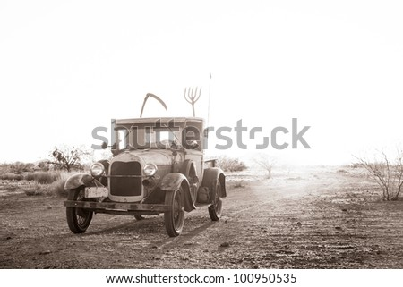 Classic truck (1928) driving on a dusty road in the desert.