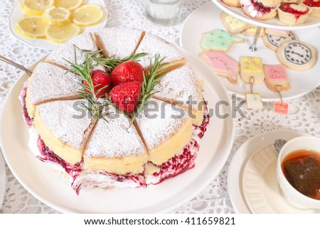 Classic Victoria sponge cake and other desserts served at the tea party, selective focus on the strawberries. Afternoon's high tea in Alice's mad tea party concept. - stock photo