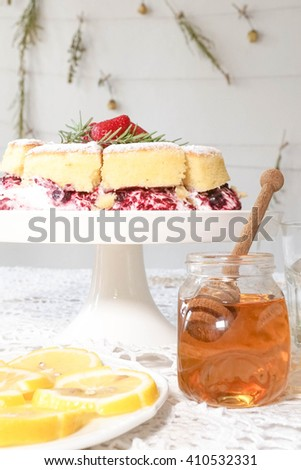 Classic victoria sponge cake, Honey and Lime served at the tea party, selective focus on the honey dropper (brighter tone) - stock photo
