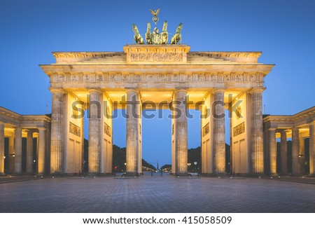 Classic view of famous Brandenburg Gate, Germany's most famous landmark and a national symbol, in twilight during blue hour at dawn with retro vintage Instagram style filter effect, Berlin, Germany - stock photo