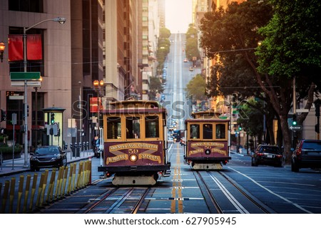Classic view of historic traditional Cable Cars riding on famous California Street in morning light at sunrise with retro vintage style cross processing filter effect, San Francisco, California, USA