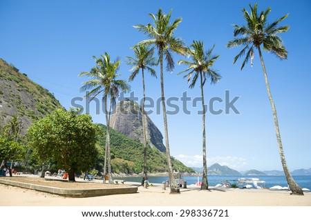 Classic view of Sugarloaf Mountain Pao de Acucar Rio de Janeiro Brazil and Praia Vermelha Red Beach at Urca with palm trees - stock photo
