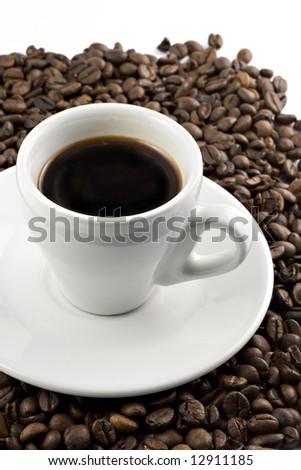 Classic white espresso cup on coffee beans - stock photo