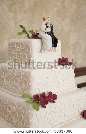 Classic white wedding cake with figurines at reception - stock photo