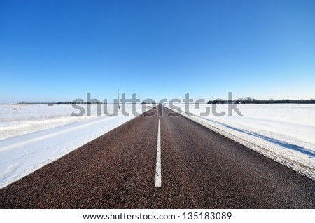 classic winter scene of a highway in rural area - stock photo