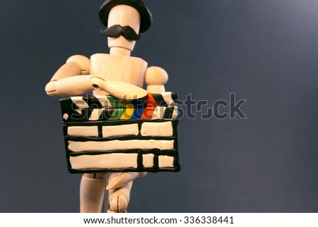 Classic wooden dummy holds a cinema clapper, hat and mustache for true filmmakers.