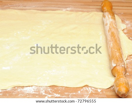 Classic wooden rolling pin with freshly prepared dough and dusting of flour. - stock photo