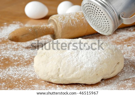 Classic wooden rolling pin with freshly prepared dough and retro flour shaker.  Shallow dof.  Selective focus on shaker and dough. - stock photo