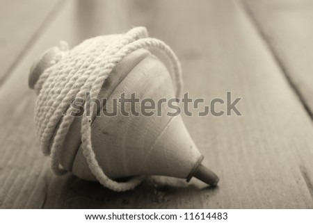 Classic wooden top toy with string, sepia tone - stock photo