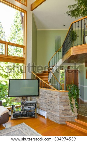 Classic wooden trim of beautiful living room interior with hardwood floor. Living room with wooden up stairs leading to the upper floor.
