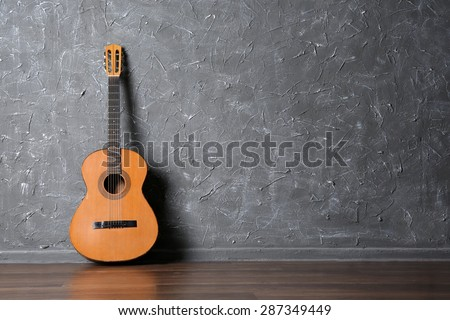 Classical acoustic guitar on gray wall background - stock photo