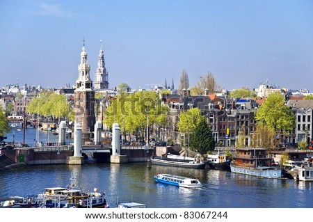 Classical Amsterdam view. Boat floats on the channel on the background of bridge. Urban scene. - stock photo