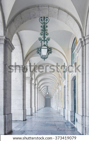 Classical architecture in a white marble archway with green lamps