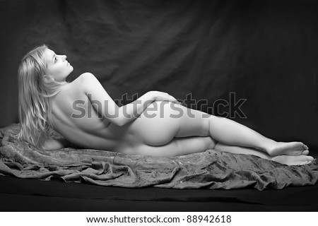 Classical artistic style picture of a woman posing on black background. - stock photo