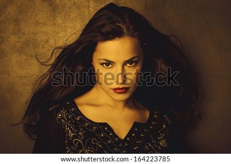 classical beauty young long hair brunette woman in embroidered shirt in golden tones - stock photo