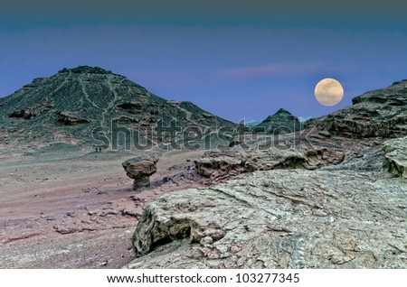 Classical biblical landscape with rise of supermoon in desert of the Negev, Israel - stock photo