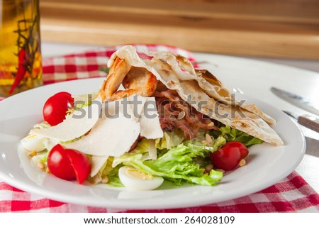 Classical Caesar salad with  roasted chiken, quail eggs, lettuce leaves, crackers, parmesan slices and cherry tomatoes decorated with peanuts served in white round  plate - stock photo