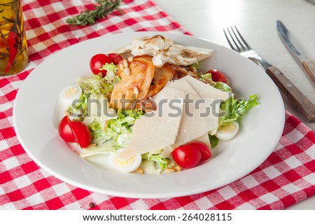 Classical Caesar salad with  roasted chiken, quail eggs, lettuce leaves, crackers, parmesan slices and cherry tomatoes decorated with peanuts served in white round  plate