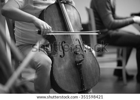Classical cello music, mid section of a musician playing - stock photo