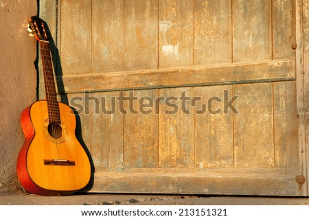 classical guitar leaning on old door illuminated by the setting sun