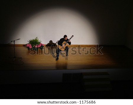 Classical guitarist performing on stage - stock photo