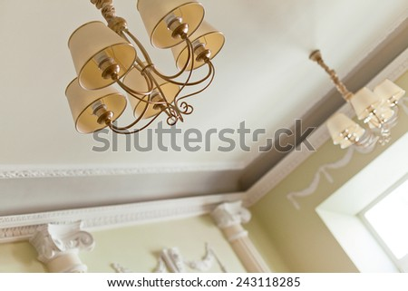 Classical interior of a ceiling with a classical chandelier - stock photo