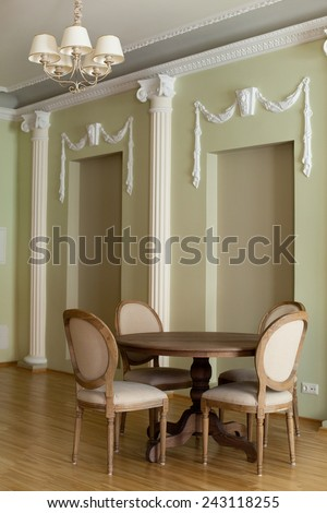 Classical interior of a dining room with round dining table and chairs around - stock photo