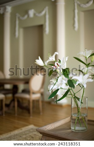 Classical living room interior with dining table and lilies in the vase - stock photo
