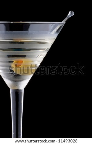 Classical martini in chilled glass over black background on reflection surface, garnished with olive. Most popular cocktails series.