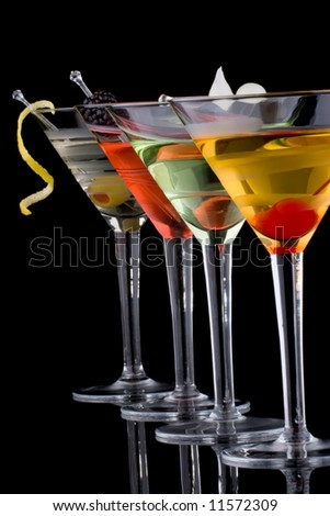 Classical martini in chilled glass over black background on reflection surface, garnished with fresh blackberry, maraschino cherry, marinated pearl onoions, olive and lemon twist. - stock photo