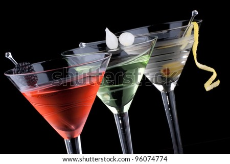 Classical martini in chilled glass over black background on reflection surface, garnished with fresh blackberry, marinated pearl onions, olive and lemon twist. Most popular cocktails series. - stock photo