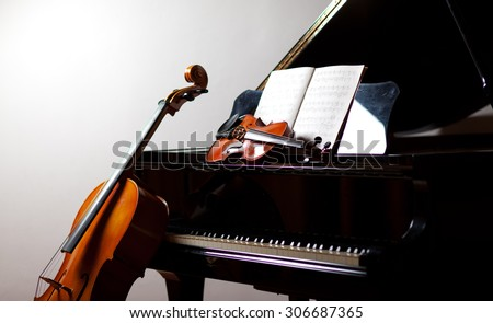 Classical music concept: cello and violin leaning on a piano - stock photo