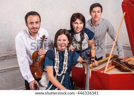 Classical music quartet posing after the concert with their instruments in hall, smiling and looking at camera at white background. Casual style. Studio shot. - stock photo
