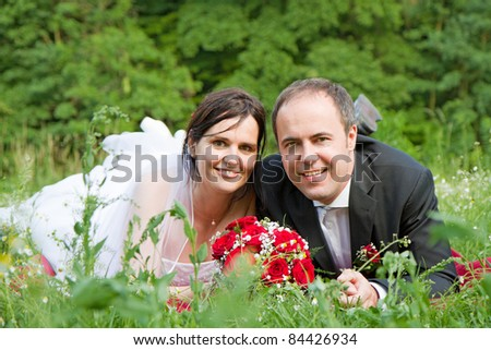 classical newly wed couple with wedding gown dark suit and red bridal bouquet the groom and  bride lie on a meadow