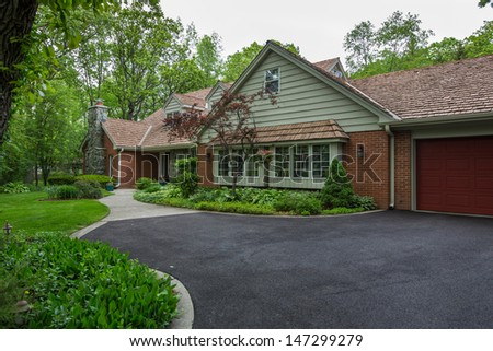 Classical North American Residential House in Wooded Area in Fall Season - stock photo