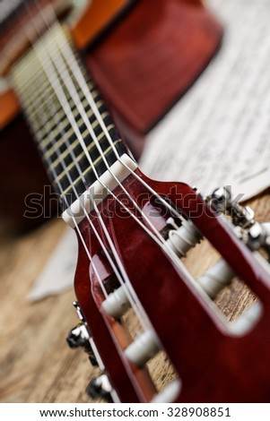 Classical nylon string guitar with sheet music - stock photo